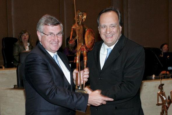 Sr. Marco Antonio Rossi, diretor-presidente da Bradesco Seguros, recebendo o troféu Dom Quixote das mãos do Sr. Ivan Luiz Gontijo Júnior, diretor jurídico da Bradesco Seguros